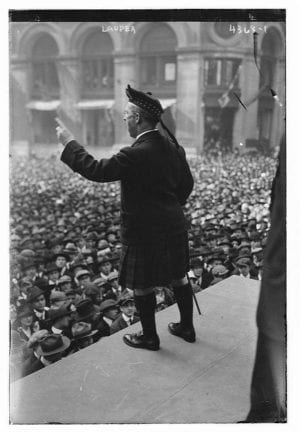 A black and white photo of a man wearing a kilt, on a stage speaking to a large crowd
