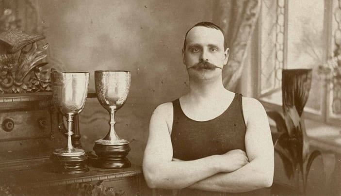 A sepia photo, from the Australian National Maritime Museum, circa 1905, of a magnificently moustached man in a swimming costume, standing by two trophies