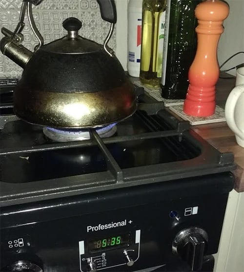 A photo of a kettle on a hob with a digital clock showing 5:35am