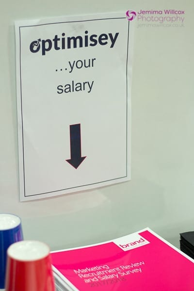 "A photo showing a stack of Brand Recruitment's salary survey brochures, under a poster saying ""Optimisey... your salary"""