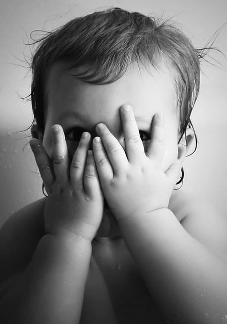 A black and white photograph of a young child hiding behind their hands