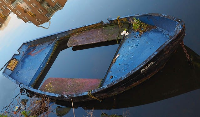 A photo of an old blue rowing boat, called Astoria, filled with water