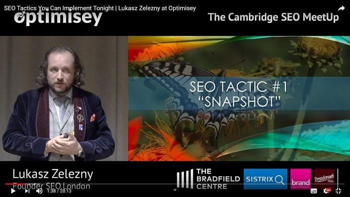 A screenshot of a video of Lukasz Zelezny talking at the Optimisey SEO event